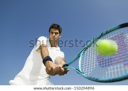 Low angle view of determined young man playing tennis against blue sky #150204896