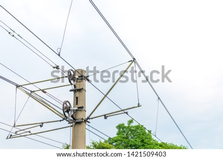 Low angle view of electric cable and pole over railway or railroad against cloudy sky. #1421509403