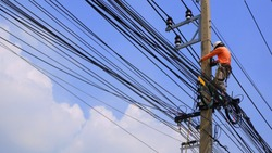 Low angle view of electrician lineman working to install electrical system on electric power pole against white cloud and blue sky background, technology and development concept