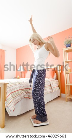 Low angle view of excited woman standing in her bedroom and looking down at a scale. Vertical format.