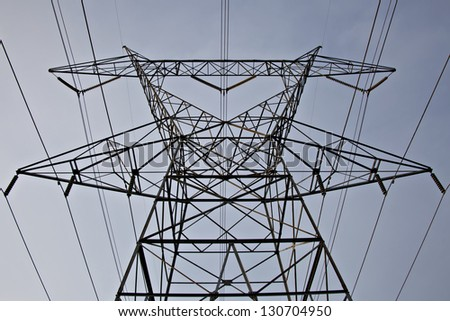 Low angle view of extremely tall electrical tower and power lines