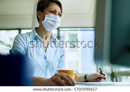 Low angle view of female entrepreneur wearing face mask while working on a computer and writing notes in the office.