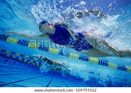 Low angle view of female swimmers gushing through water in pool