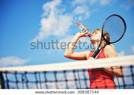 Low angle view of female tennis player drinking a water .Shallow doff, copy space