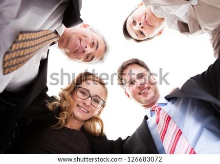 Low angle view of four diverse business executives looking down into the camera from above isolated on white