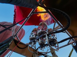 Low angle view of gas burner with its flames from the inside of a hot air balloon basket