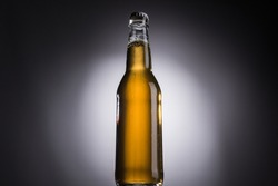 low angle view of glass bottle with beer on dark background with back light