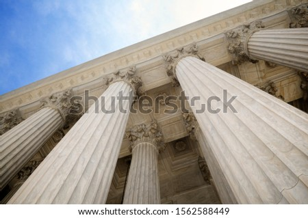 Low angle view of grand classical stone columns soaring up to decorative entablature at a Court building in Washington DC, USA ストックフォト ©
