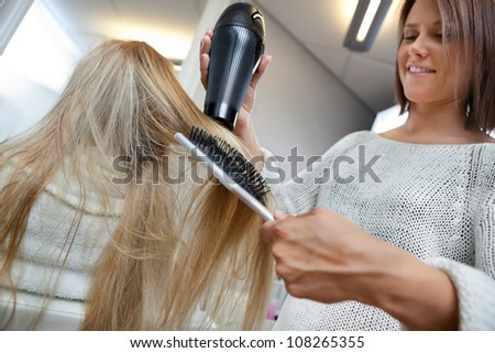 Low angle view of hairdresser drying long blond hair with blow dryer and brush