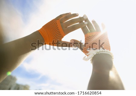 Low angle view of hands making a shield from the sun