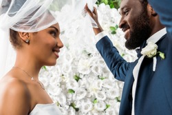 low angle view of happy african american bridegroom touching white veil and smiling near bride and flowers