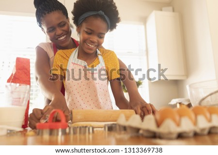 Low angle view of happy African American mother and daughter baking cookies in kitchen at home. Social distancing and self isolation in quarantine lockdown for Coronavirus Covid19