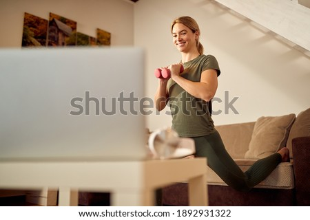 Low angle view of happy athletic woman using laptop while practicing with hand weights n the living room. Foto stock ©