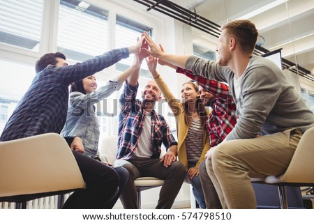 Low angle view of happy creative business people giving high-five in meeting room at creative office #574798510