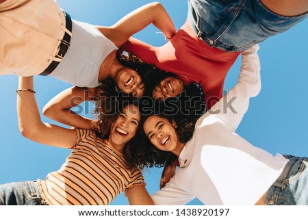 Low angle view of happy female friends with curly hair standing in circle and looking at camera. Girls in a hurdle looking down and laughing.