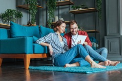 low angle view of happy man and woman looking at digital tablet in living room