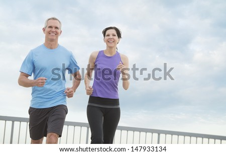 Low angle view of happy mature couple jogging against cloudy sky