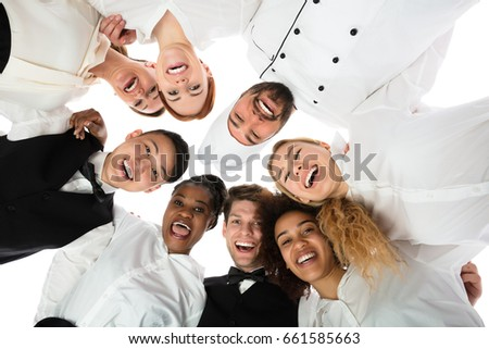 Low Angle View Of Happy Restaurant Staff Standing Against White Background #661585663