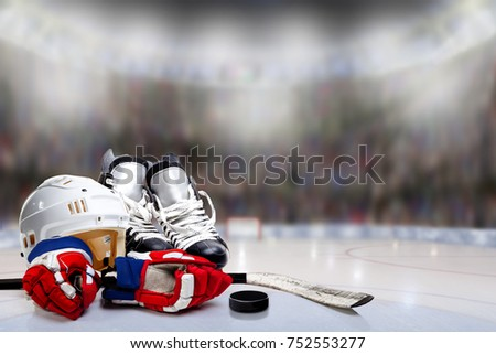 Low angle view of hockey helmet, skates; gloves; stick and puck on ice with deliberate shallow depth of field on brightly lit stadium background and copy space.