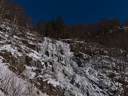 Low angle view of icy water fall Todtnauer Wasserfälle in winter season with icicles and snow on rocks surrounded by bare trees on sunny winter day with blue sky near Todtnau, Black Forest, Germany.