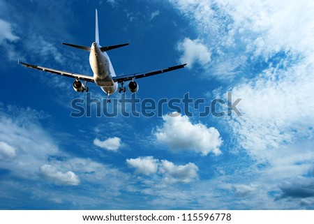 low angle view of landing aircraft on blue sky