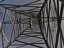 Low angle view of lattice steel power pole (also transmission tower) used to support overhead power lines in Ostfildern near Stuttgart, Germany with cloudy sky.