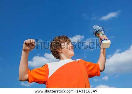 Low angle view of little boy celebrating victory while holding trophy against sky