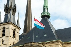 Low angle view of Luxembourgian flag against towers of the Cathedral of the Blessed Virgin in Luxembourg City, Luxembourg.