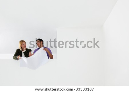 low angle view of male architect and woman examining blueprints. Copy space