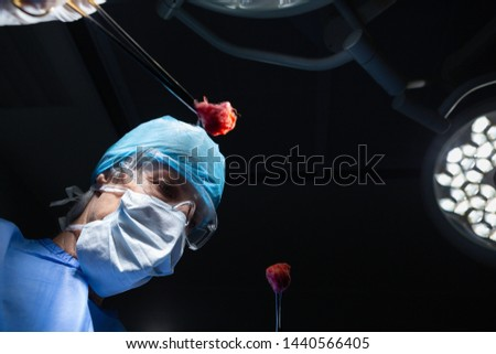 Low angle view of mature Caucasian female Surgeon performing operation in operation room. She is holding surgical forceps with cotton in the hospital