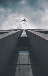 Low angle view of modern tall business building. Commercial jet plane flying over skyscraper. Against dramatic cloudy sky before storm.