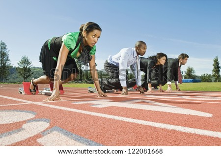 Low angle view of multi ethnic business people at starting position on race track