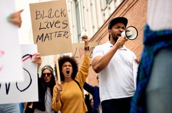 Low angle view of multi-ethnic group of people supporting Black Lives Matter movement and protesting on city streets.