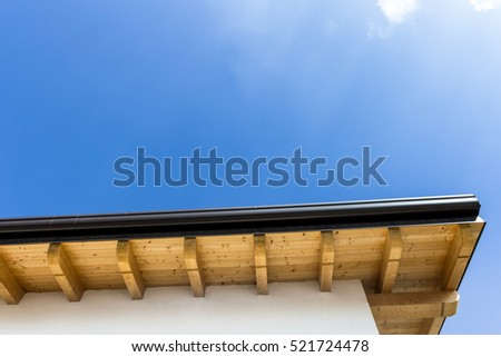 Low angle view of new house with wooden roof and gutter against clear blue sky #521724478