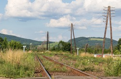 Low angle view of old railway track. Division of double-track line to different directions. Long row of telegraph poles leading to next station. Summer sunny evening time.