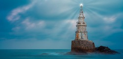 Low angle view of old white lighthouse tower isolated in calm blue sea water after sunset near Ahtopol on Black sea coast,Bulgaria. Landscape of lighthouse emitting light and rays. Long exposure
