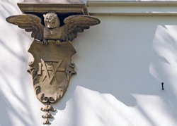 Low angle view of owl with escutcheon statue on wall of Art Nouveau villa.