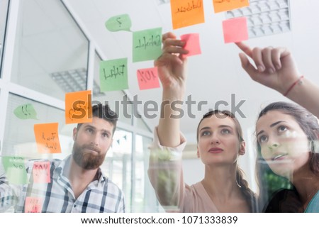 Low-angle view of reliable young workers posting reminders on the transparent wall of an office, next to their colleague in a modern co-working space
