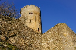 Low angle view of remnants of the royal fortress of Najac, France, former capital of Rouergue, with the massive round dungeon-tower, having crenellations and arrow splits, and stone wall remparts