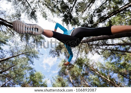 low angle view of runner jumping and running in forest. healthy active lifestyle