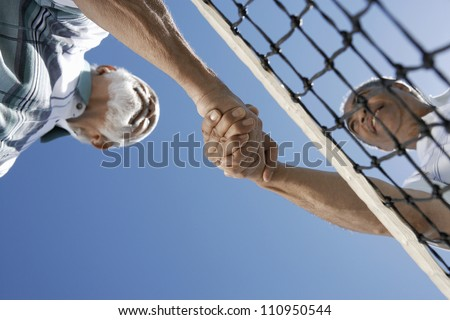 Low angle view of senior tennis players shaking hands against clear sky