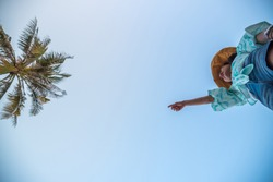 Low angle view of sexy woman short jeans midair by jumping, crossing step over camera shot below at beach with coconut and sky overhead in concept travel, active lifestyle, overcome obstacles in life