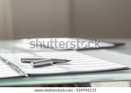 Low angle view of silver ink pen lying on white sheet of paper in a folder with another set of paperwork at the opposite side of the desk.