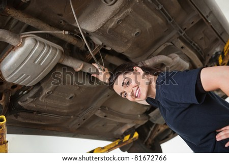 Low angle view of smiling young female mechanic repairing car in auto repair shop