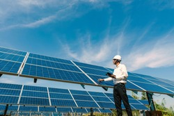 Low angle view of solar farm(solar panel) with engineers check the operation of the system, Alternative energy to conserve the world's energy, Photovoltaic module idea for clean energy production.