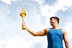 Low angle view of sportsman holding a cup against blue sky