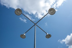 Low angle view of street lamp post against blue sky and cloud.