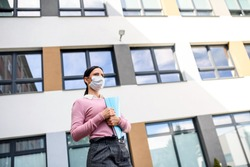 Low angle view of teacher with face mask after lockdown, walking in front of school.