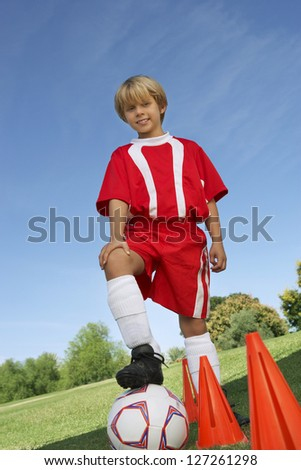 Low angle view of teenage boy standing with soccer ball against clear sky #127261298