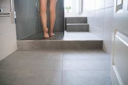 Low angle view of the bare legs of a young woman stepping into a shower cubicle to wash in a modern tiled bathroom